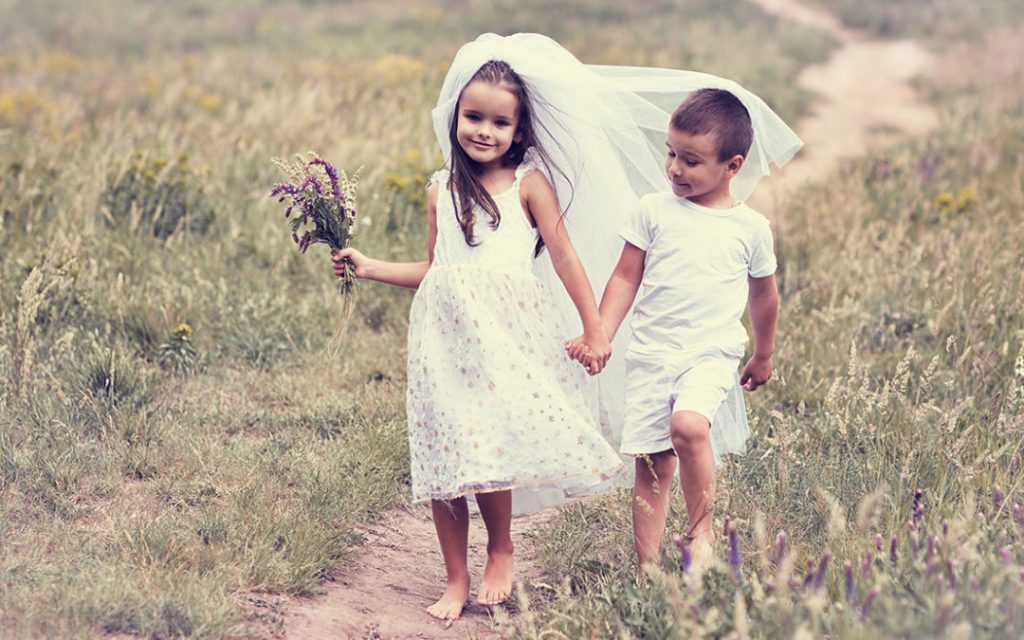 Young bride and groom playing wedding summer outdoor. Children like newlyweds. Little girl in bride whote dress and bridal veil kissing her little boy groom, kids game. Bridal, wedding concept, image toned and noise added.