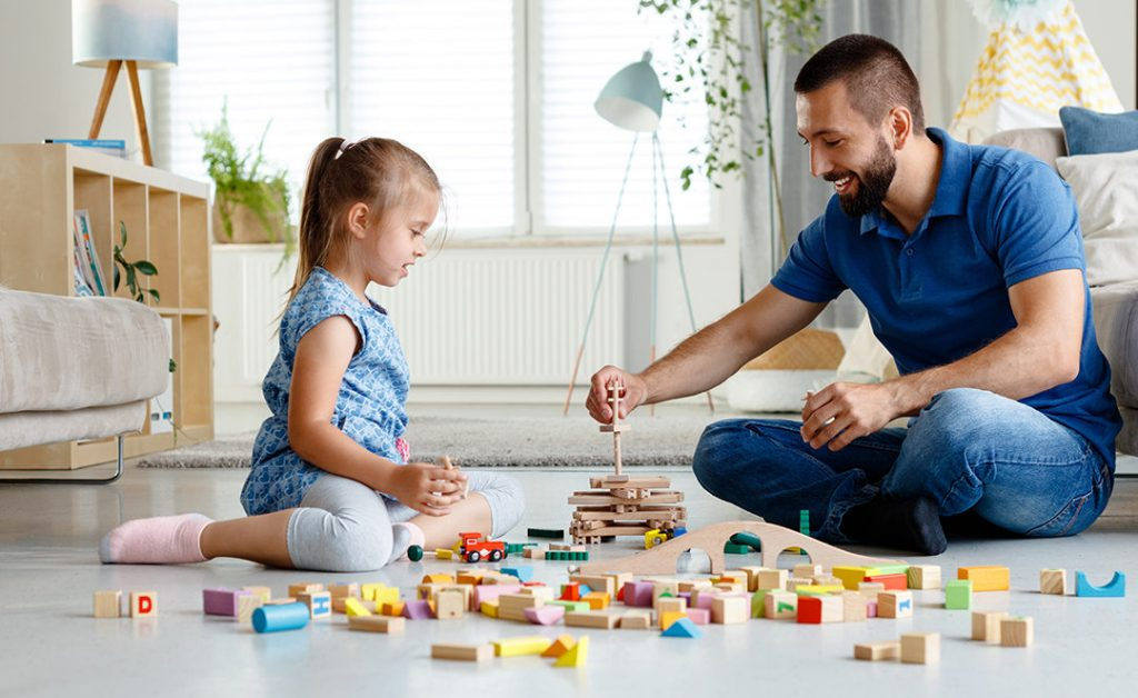 Father with his daughter playing with blocks together at home, sitting on the floor in the living room.