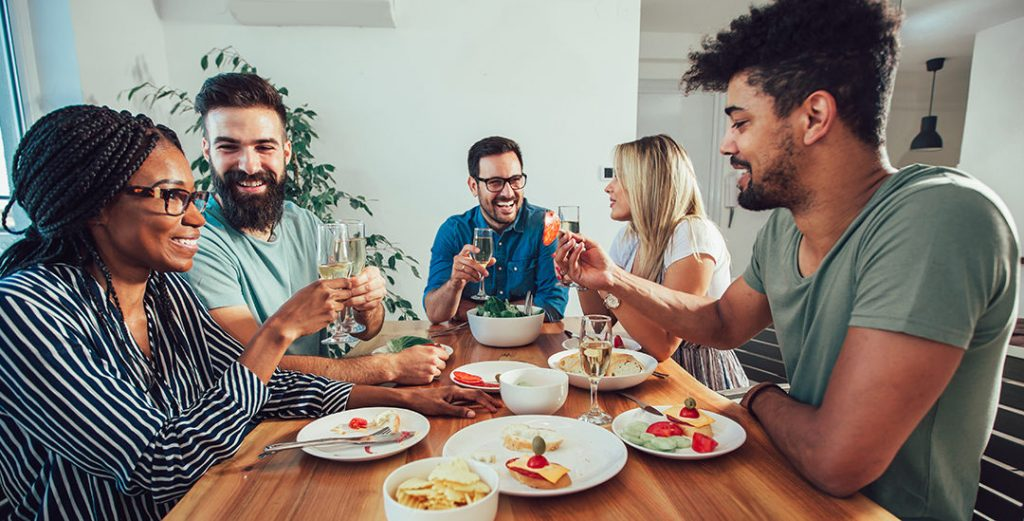 Group Of Happy Young Friends Enjoying Dinner At Home. Group of multiethnic friends enjoying dinner party