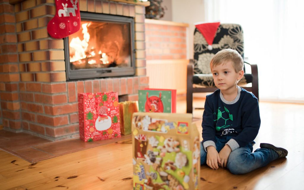 5 years old boy sits in front of the fireplace and is sad with Christmas gifts.