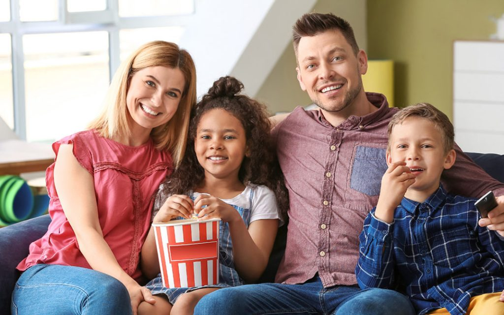 Happy couple with little adopted children eating popcorn while watching TV at home