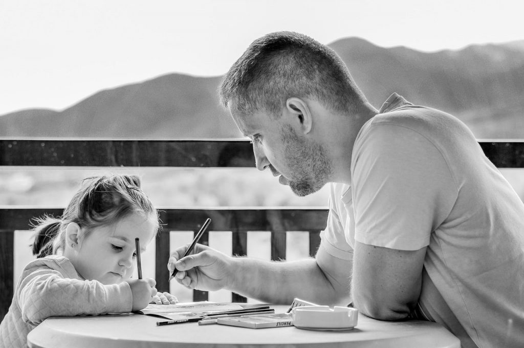 Daughter drawing with her father together
