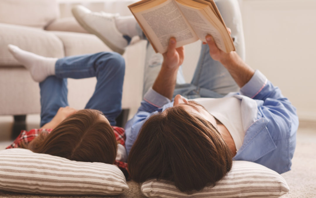 Little girl and father enjoying book together, laying on floor, parenting time