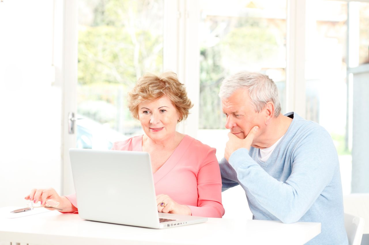 An older couple is looking at computer together