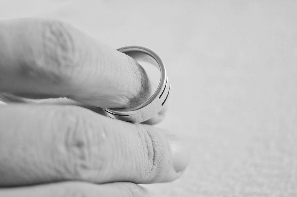 Hand holds a marriage ring, plan to divorce