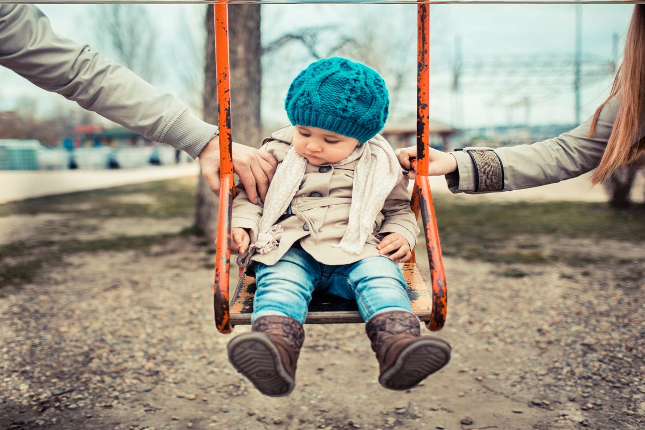 Kid on swing, mom and dad hold from each side,