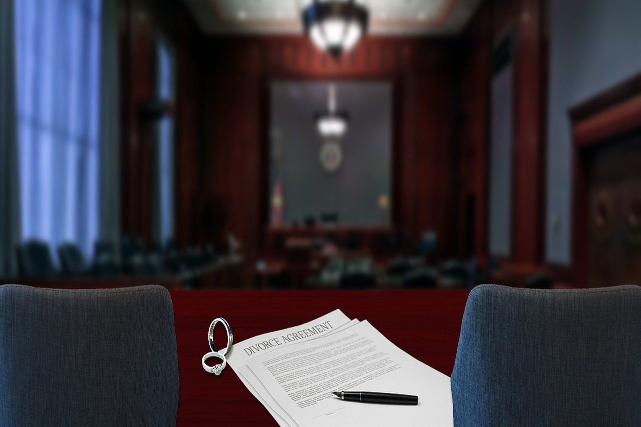 Divorce agreement and marriage rings in a court room