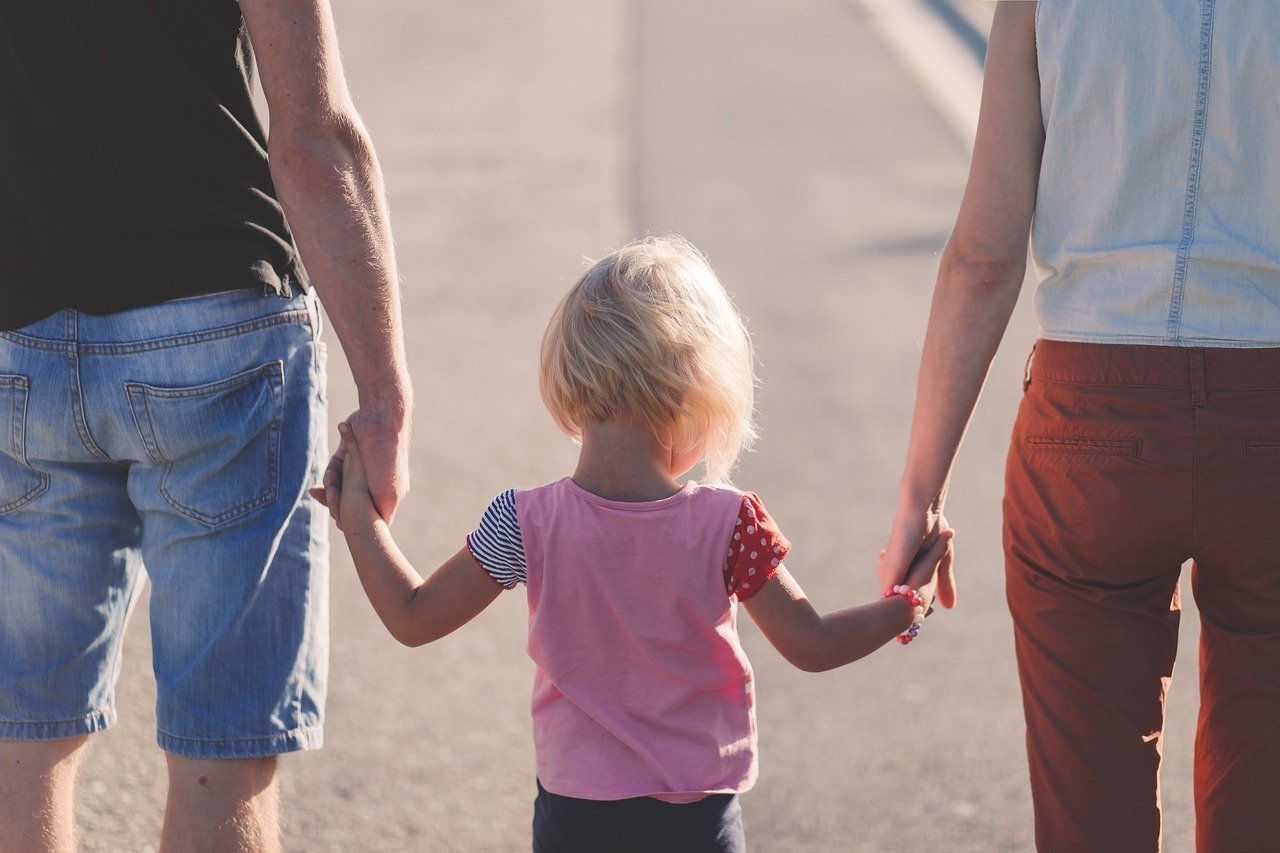 Parents hold a girl hands, family time