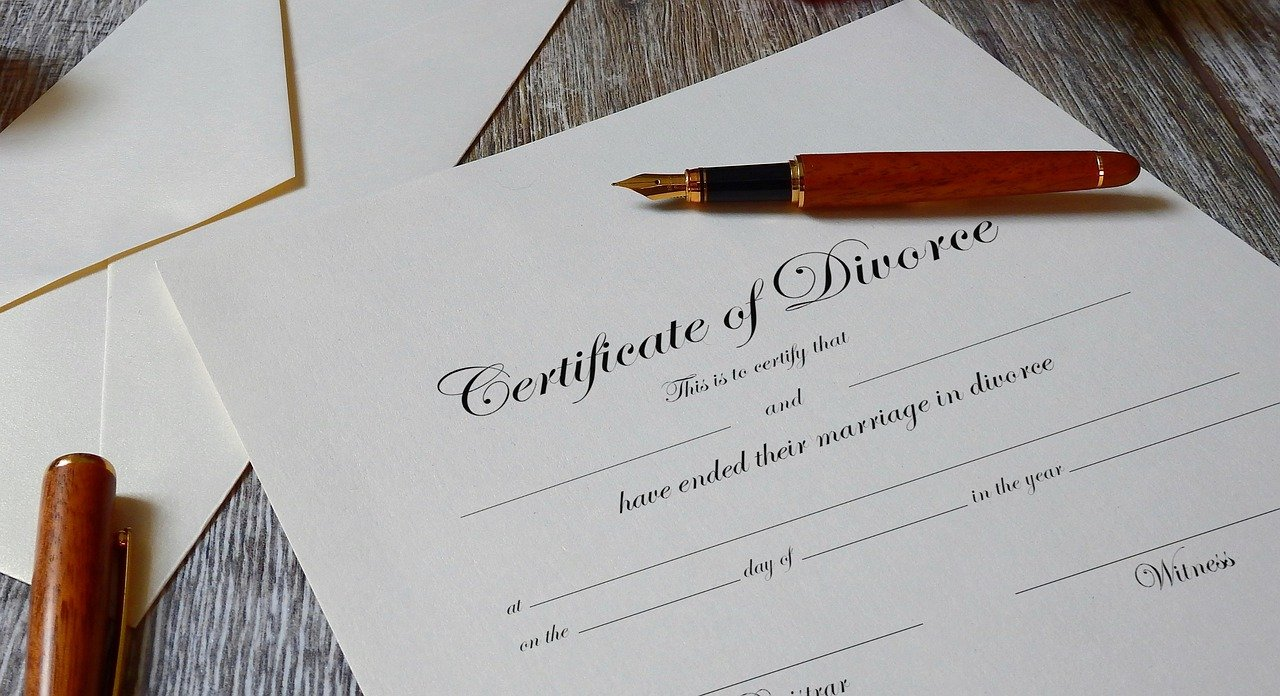 A certificate of divorce paper with a pen